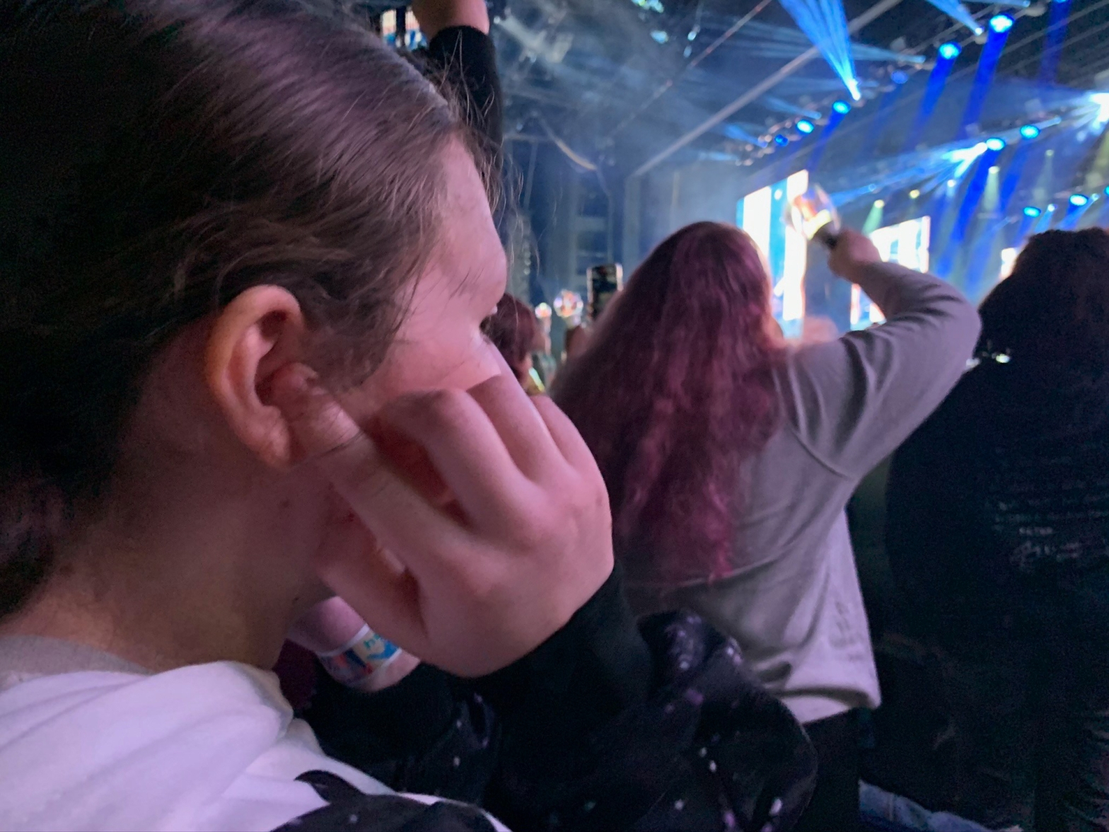 Photo of child with fingers in ears watching a concert